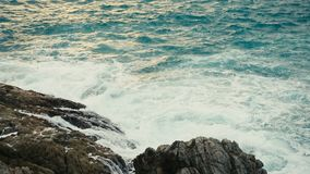 Ocean waves breaking on a rocky shore at sunset stock video