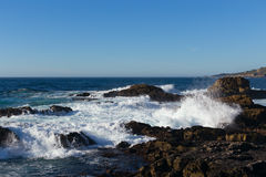 Ocean waves breaking on shoreline rocks Royalty Free Stock Images