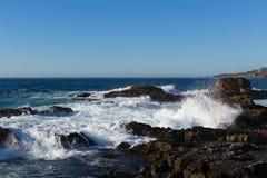 Ocean waves breaking on shoreline rocks Royalty Free Stock Images
