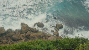 Ocean waves breaking on the stone cliffs. Aerial top view of Tropical beach Bali, Indonesia. Slow motion. Ocean waves breaking on the stone cliffs. Aerial top stock footage