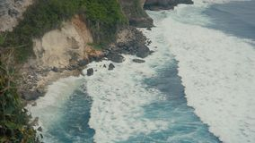 Ocean waves breaking on the stone cliffs. Aerial top view of Tropical beach Bali, Indonesia. Slow motion. Ocean waves breaking on the stone cliffs. Aerial top stock video