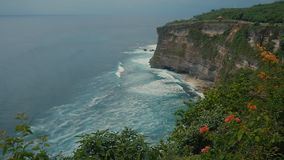 Ocean waves breaking on the stone cliffs. Aerial top view of Tropical beach Bali, Indonesia. Slow motion. Ocean waves breaking on the stone cliffs. Aerial top stock video footage