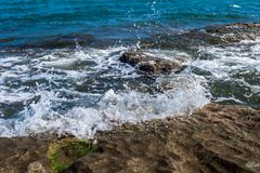 The wave breaks on the rock. The waves breaks on the rock stock images