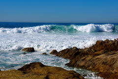 Background Rocks and Waves. The deep blue sky above the teal blue of the ocean is offset by the white foam of the wave action as it surges onshore at Carmel Royalty Free Stock Photos
