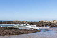 Ocean Waves Coming to Shore over Rocks and Sand Royalty Free Stock Image