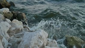 Ocean waves crash over a rocky shore. Slow mothion HD 100 FPS stock video footage