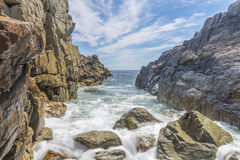 Ocean waves crashing against a rocky shore- slow shutterspeed Stock Photo