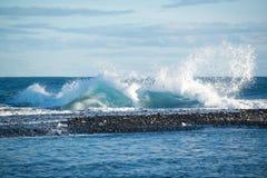 Ocean waves crashing on icebergs, black sand beach at Jokulsarlon, Iceland Stock Images