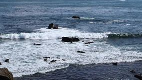 Ocean waves crashing on rocks. And the rocky shore. Filmed in Laguna Beach, Orange County, California on a summer day stock footage