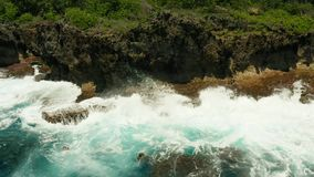 Ocean with waves crashing on the shore. Seascape: blue ocean and surf waves crashing on rocky coastline slow motion, top view. Siargao, Philippines. Summer and stock video