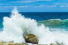 Ocean Waves Crashing Spray Coastline. Ocean  waves crashing water power spay along rocky coastline summer landscape Stock Photos