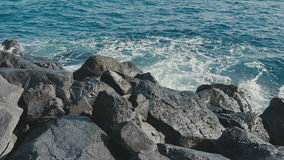 Ocean waves crashing on stone beach stock video footage