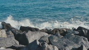 Ocean waves crashing on stone beach stock footage