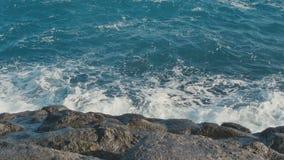 Ocean waves crashing on stone beach stock video