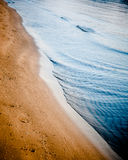 Ocean waves gently touching the sandy shore Royalty Free Stock Photography