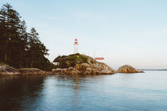 Ocean waves hitting rocks on coast and lighthouse in background Royalty Free Stock Photos