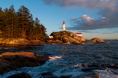 Ocean waves hitting rocks on coast and lighthouse in background Royalty Free Stock Image
