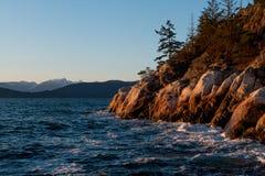 Ocean waves hitting rocks on coast while sunset Royalty Free Stock Images