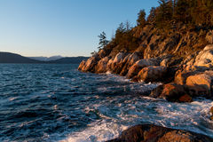 Ocean waves hitting rocks on coast while sunset Stock Photo