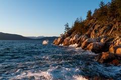 Ocean waves hitting rocks on coast while sunset Royalty Free Stock Photos