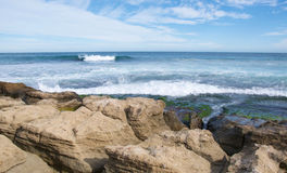 Ocean Waves: Peaceful Penguin Island. Indian Ocean swell rolling in at Penguin Island with natural limestone rock formations under a blue sky with clouds in Stock Photography