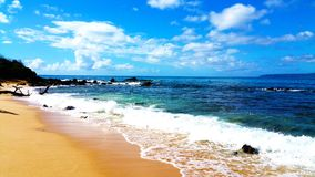 Ocean waves rocks blue skies and a beautiful beach Royalty Free Stock Photography