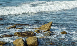 Ocean Waves and Rocks. Blue water waves and ocean rocks near the shore Royalty Free Stock Photography
