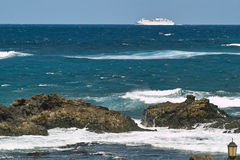 Ocean waves, rocks and white ferryboat Stock Photography