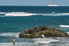Ocean waves, rocks and white ferryboat Royalty Free Stock Photo