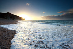 Ocean waves on rocky beach at sunset Stock Photo