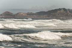 Ocean waves and rocky hillside shore Stock Image