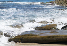 Ocean waves on rocky shoreline. Clear blue water movement onto sandy shore with boulders Royalty Free Stock Images