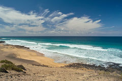 Ocean waves rolls on the footprints on sandy beach Royalty Free Stock Image