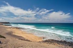 Ocean waves rolls on the footprints on sandy beach Royalty Free Stock Photo