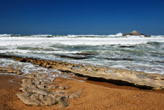 Ocean waves running on smooth rocks at the time of ebb. Royalty Free Stock Images