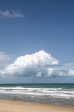 Ocean waves with sandy beach and cumulus cloud Stock Photo