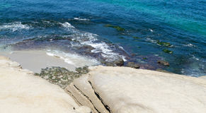 Ocean waves on shoreline of beach and rocks Royalty Free Stock Image
