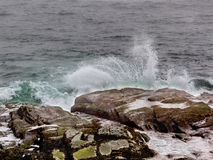 Ocean waves splash against shore rocks in Jamestown Rhode Island. Ocean waves splash against rocks in Beavertail on a cloudy day royalty free stock photos