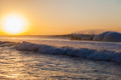 Ocean Waves Spray Wash Sunrise. Ocean waves at sunrise surging and crashing on high tide with swells breaking large powerful volumes of sea water washing towards Royalty Free Stock Photo