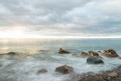 Ocean waves at sunrise - Long-exposure Stock Photo