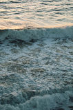 Ocean waves at the sunset on the coast Stock Images