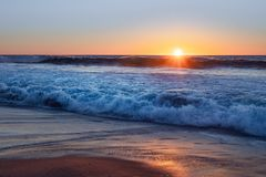 Sunset on the beach, California. Ocean waves during sunset, yellow and blue background, beautiful seascape, California royalty free stock photo