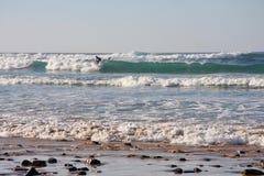 Ocean waves and surfer. Light blue sky. Atlantic ocean coast.Portugal, Faru Stock Photo