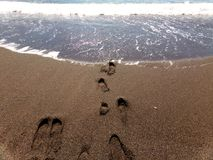 Ocean Waves Washing Over Footprints In The Sand Of The California Coast Stock Photo