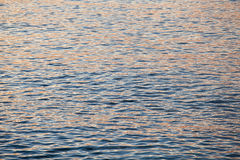 Ocean waves and the water surface at sunset. With the reflection of the sun Royalty Free Stock Photos