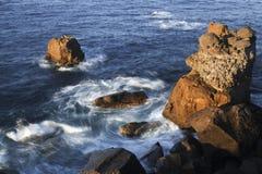 Ocean wiruje wokoło skalistego wychodu Obraz Royalty Free