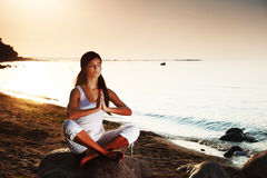 Ocean yoga sunrise. Young woman practicing yoga  near the ocean Royalty Free Stock Photography