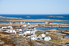 Oceanfront Property. Newfoundland Coast showing Fishing Village among Rugged, Wind Swept Bedrock and Red vegetation Stock Images