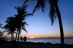 Oceanfront  Tropical Sunset. An oceanfront tropical sunset with a silhouette of a family in the distance Stock Image