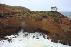 Stormy waves eroding high cliff. A characteristic Australian coastal landscape at a stormy day. Waves surging against the cliff in a huge basin (at Snappers Stock Photos